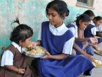 An Indian schoolgirl feeds her younger s